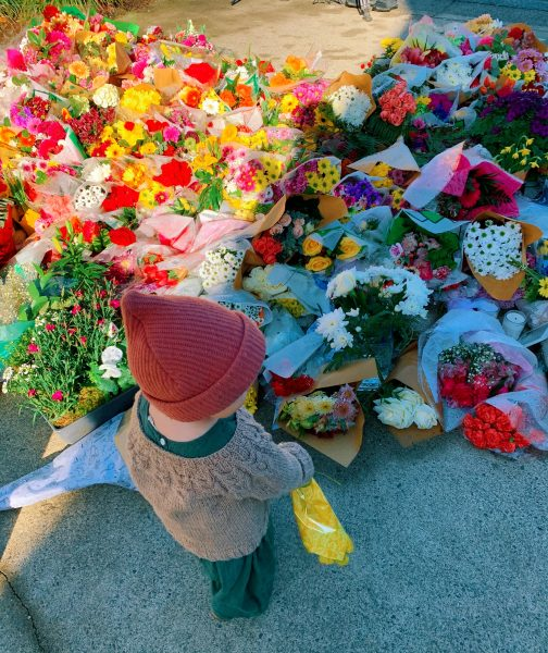 young girl placing flowers at the memorial at lynn valley public library