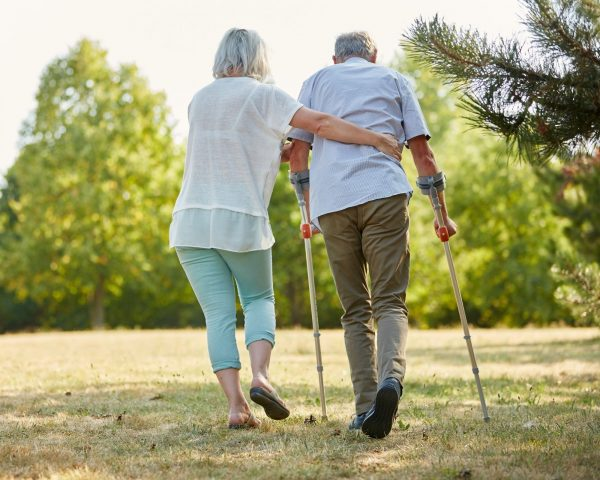 two people walking side by side, one has walking aids and the other person has their arms wrapped around that person, helping them to move